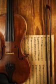 Old used violin on wooden board with note — Stock Photo