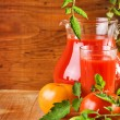 Jug and glass with tomato juice and tomatoes — Stock Photo