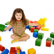 Little girl playing with color cubes on floor — Stock Photo
