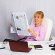 Young woman reads news on the workplace — Stock Photo