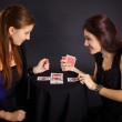 Photo: Two girls friends engaged in fortune-telling cards