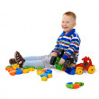 Stock Photo: Little boy sitting among toys on floor
