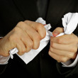 Businessman hands furiously tormenting document -  