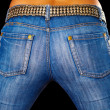 Female ass dressed in jeans on black — Stock Photo