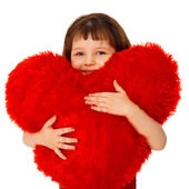 Little girl hugging a large toy heart — Stock Photo