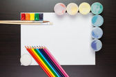 Blank sheet of paper on the brown table with colorful paints and — Stockfoto