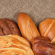 Variety of fresh bread over sackcloth background — Stock Photo