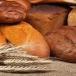 Variety of fresh bread with ears of rye background — Stock Photo