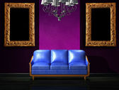 Blue leather sofa with luxury chandelier and picture frames in gallery — Stock Photo