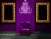 Purple chair with luxurious chandelier and picture frames in dark interior — Stock Photo