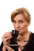 Beautiful older woman drinking coffee on a white — Stock Photo