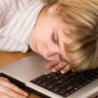 Beautiful young girl sleeping on a laptop — Stock Photo