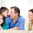 Stock Photo: Happy family on carpet