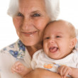 Elderly woman holding a newborn — Stock Photo
