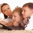 Stock Photo: Mom with his sons is on carpet