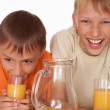 Two happy brothers drink juice — Stock Photo #5441332