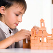 Handsome boy builds a toy castle — Stock Photo #5441363