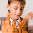 Handsome boy builds a toy castle — Stock Photo #5441366