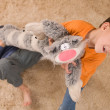 Two kids with a toy cat on the soft carpet — Stock Photo