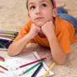 Pensive kid with pencils on the carpet — Stock Photo