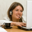 Stock Photo: Young girl with laptop, headset and cup in office