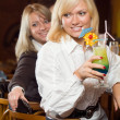 Two blonds at a bar counter with a cocktail — Stock Photo