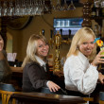 Three pretty girls at a bar counter — Stock Photo