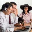 Office workers with laptops and a dog - Stock Photo