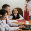 Little boy as an office-chief with employees — Stock Photo