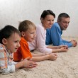 Family of four lying on the carpet — Stock Photo