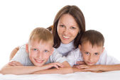 Smiling mom sitting at the desk with sons — Stock Photo
