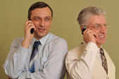 Two adult businessman standing and talking on the phone — Stock Photo