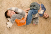 Two kids with a toy on the floor — Stock Photo