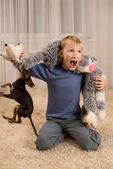 Aufgeregt kind mit spielzeug und ein hund auf dem teppich — Stockfoto