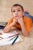 Nachdenkliches kind mit stiften auf dem teppich — Stockfoto