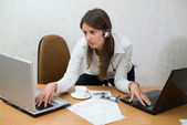 Young teen girl at the office desk with laptops — Stock Photo