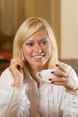 Smiling blond with a tea cup in her hand — Stock Photo