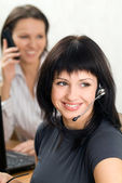 Young brunette with a headset in business — Stock Photo