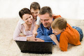 Семья, смотрящая на ноутбук — Стоковое фото