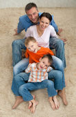 Family of four sitting on the carpet — Stock Photo