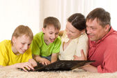 Family of four with a laptop — Stock Photo