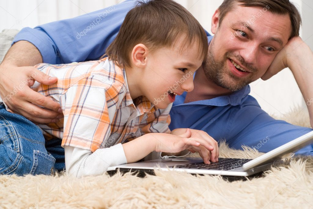 Father and son lying on the carpet with laptop  Stock Photo #5508979
