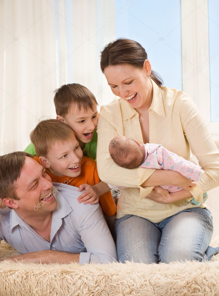 Parents of the children look at the newborn  Stock Photo #5509017
