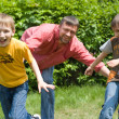 Father playing with two children - Stock Photo