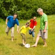 Happy family playing soccer — Stock Photo #5511176