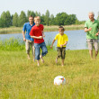 Happy family playing soccer — Stok fotoğraf