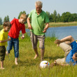 Happy family playing soccer — Stock Photo
