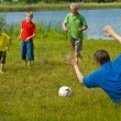 Stock Photo: Family playing soccer on the grass
