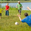 Family playing soccer on the grass — Stock Photo
