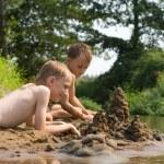 Two children build a sand castle — Stock Photo #5515001